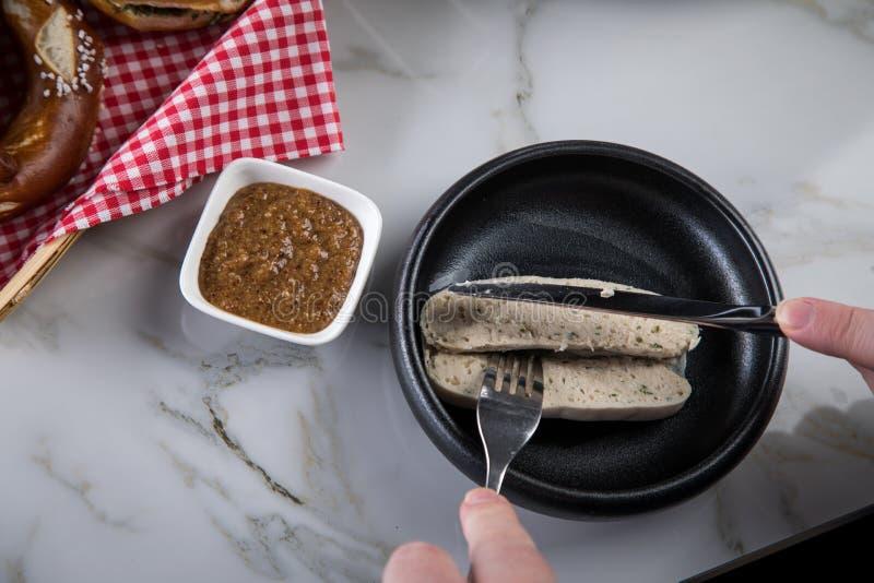 Mannen äter Munich den vita korven med kniven och gaffeln, söt senap och kringlan och att ta av korven riktigt ut ur tarmkanal royaltyfri fotografi