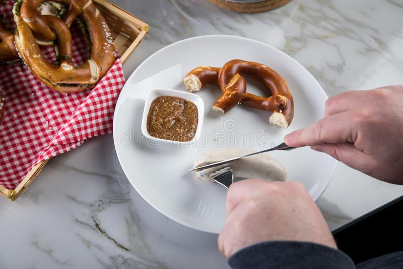 Mannen äter Munich den vita korven med kniven och gaffeln, söt senap och kringlan och att ta av korven riktigt ut ur tarmkanal royaltyfria bilder