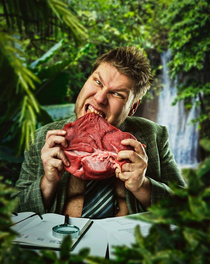 Mannen äter rött nytt kött royaltyfri foto