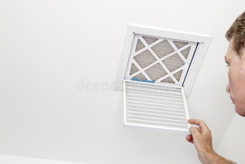 Mannen öppnade ett lufthål till ett smutsigt filter arkivbild