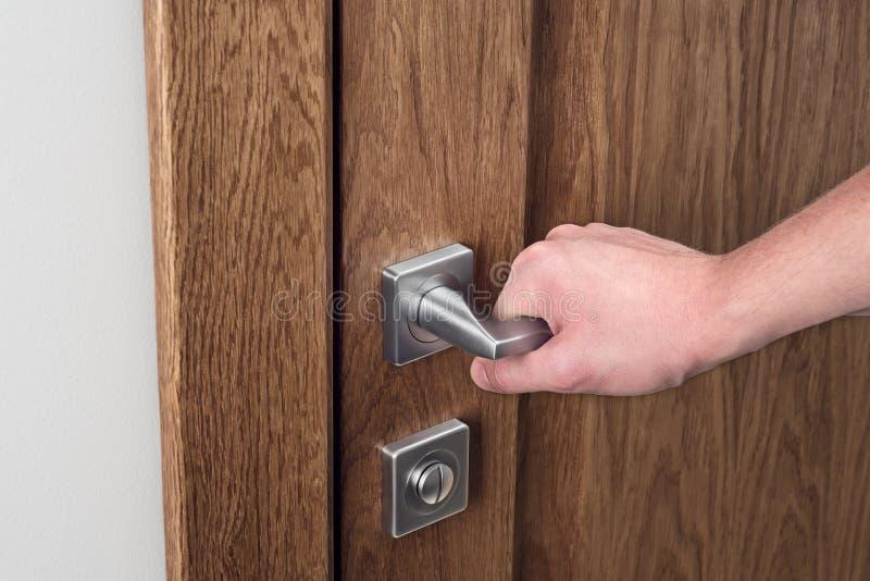 Mannen öppnar dörren Närbild av handen och dörrhandtaget arkivbild