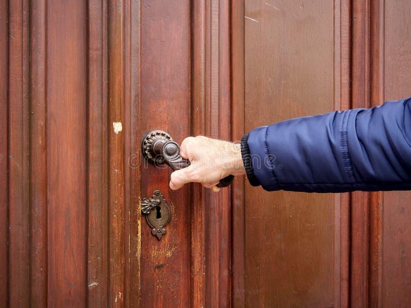 Mannen öppnar den stängda gamla dörren Gammal handtag och hand i vinter arkivbild