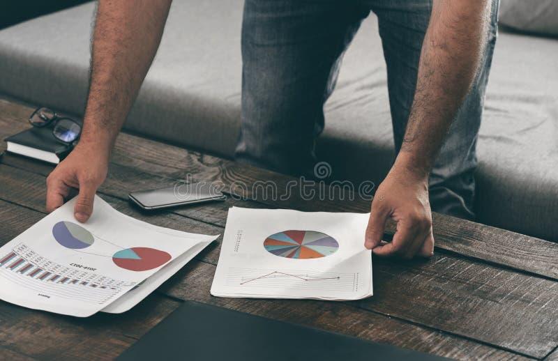 Mannen analyserar försäljningsrapporten på soffan hemma royaltyfria foton