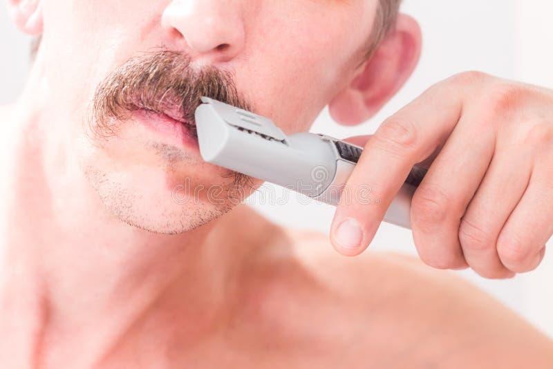 Mannen använder en beskärare för att klippa hans mustasch Närbild royaltyfria foton