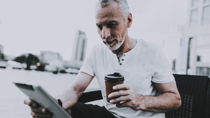 Mannen använder en minnestavlaPC och dricker ett kaffe royaltyfri fotografi