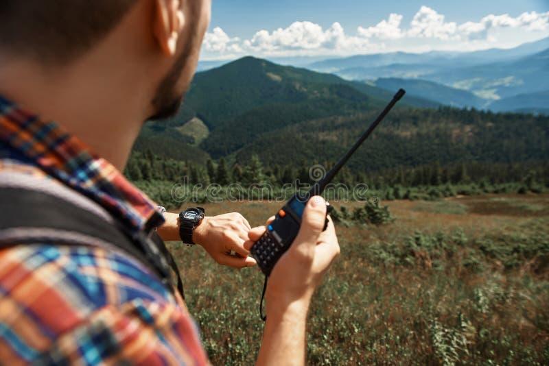 Mannen använder klockan och radion i berg arkivfoton