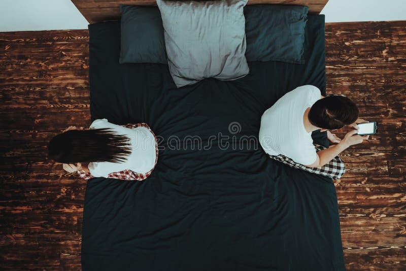 Mannen använder mobiltelefonen och kvinnan på säng royaltyfria foton