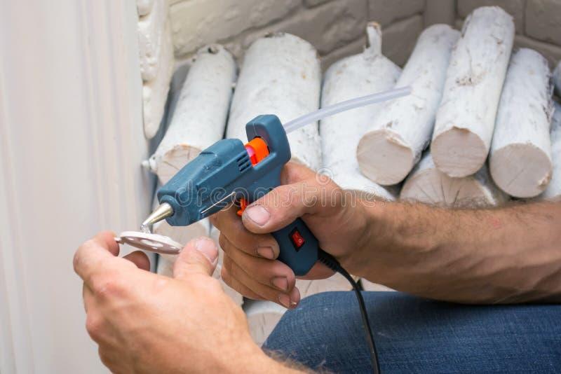 Mannen applicerar limvapnet till beståndsdelarna av den dekorativa spisen under att dekorera arkivfoton
