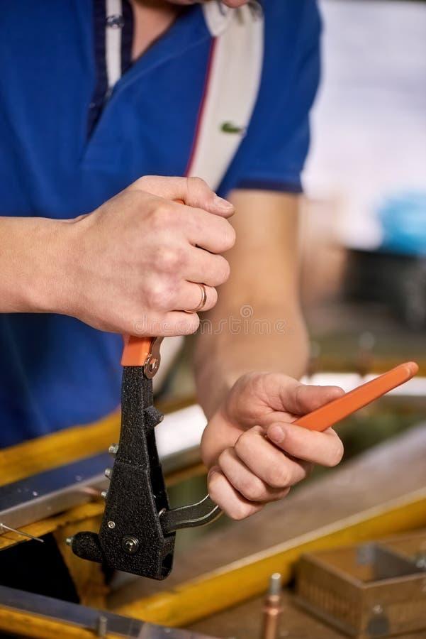 Mannen arbetar med ett popnitvapen arkivfoto