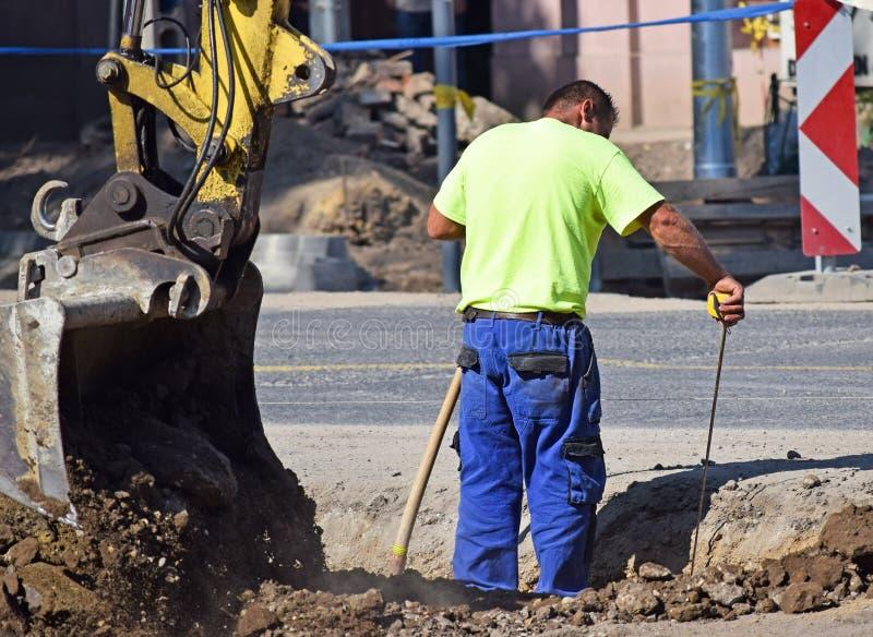 Mannen arbetar på vägkonstruktionen arkivfoto