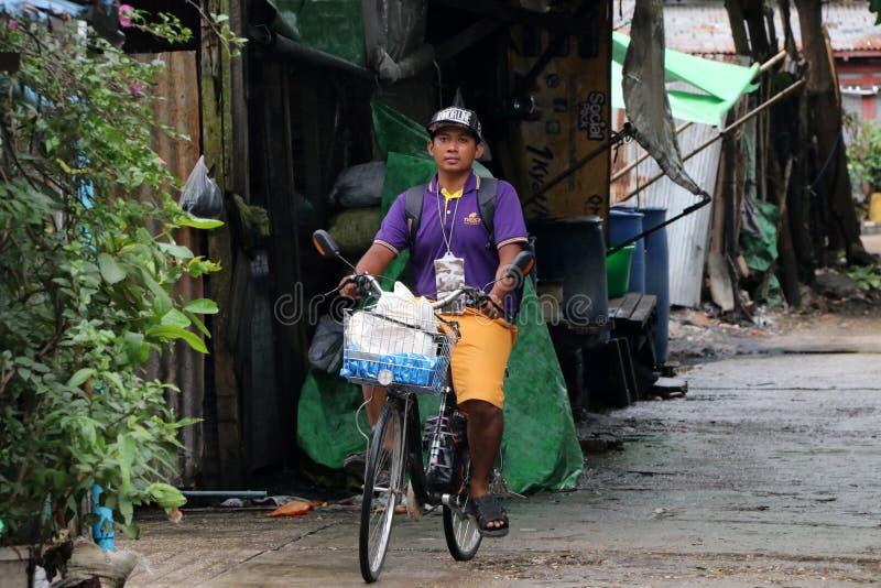 Mannen av den Myanmarese ritten en cykel på gränden av gatan i Yangon royaltyfri foto