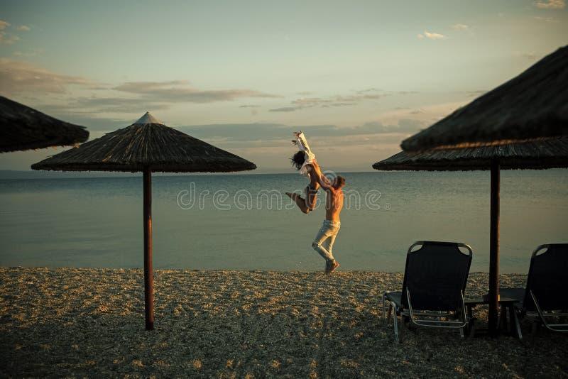 Mannen bär kvinnan, paret som är lyckligt på semester Koppla ihop den förälskade dansen och att ha gyckel-, havs- och horisontbak fotografering för bildbyråer