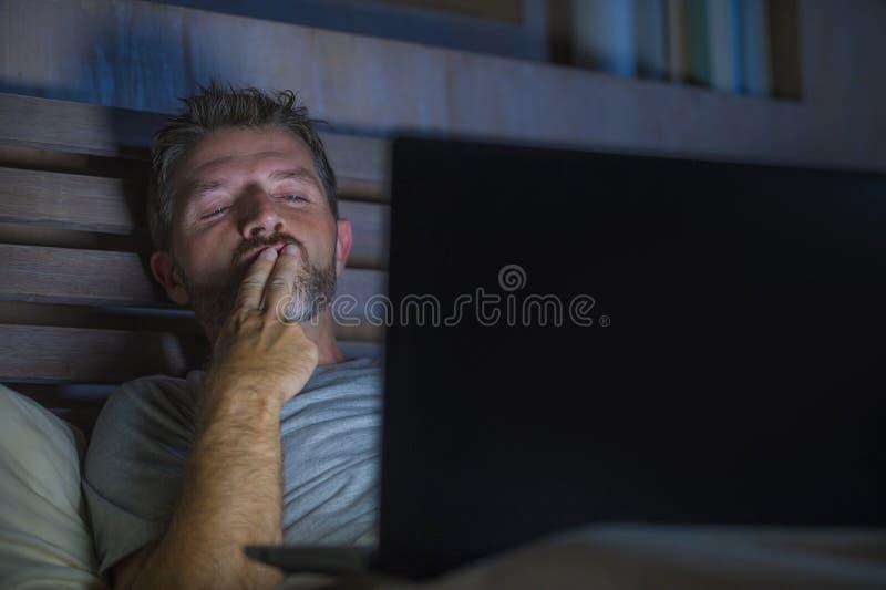 Mannen bara i säng som spelar cybersexen som använder hållande ögonen på pornografi för bärbar datordator, könsbestämmer filmen s royaltyfria bilder