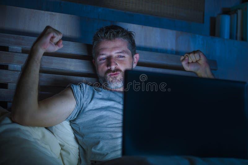 Mannen bara i säng som spelar cybersexen som använder hållande ögonen på pornografi för bärbar datordator, könsbestämmer filmen s royaltyfria foton