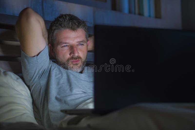 Mannen bara i säng som spelar cybersexen som använder hållande ögonen på pornografi för bärbar datordator, könsbestämmer filmen s arkivbilder