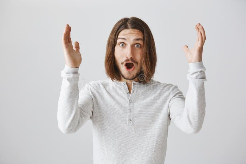 Mannen behas extremt med positiv nyheterna Den attraktiva upphetsade unga mannen med skägget och långt lyfta för hår gömma i hand arkivbilder