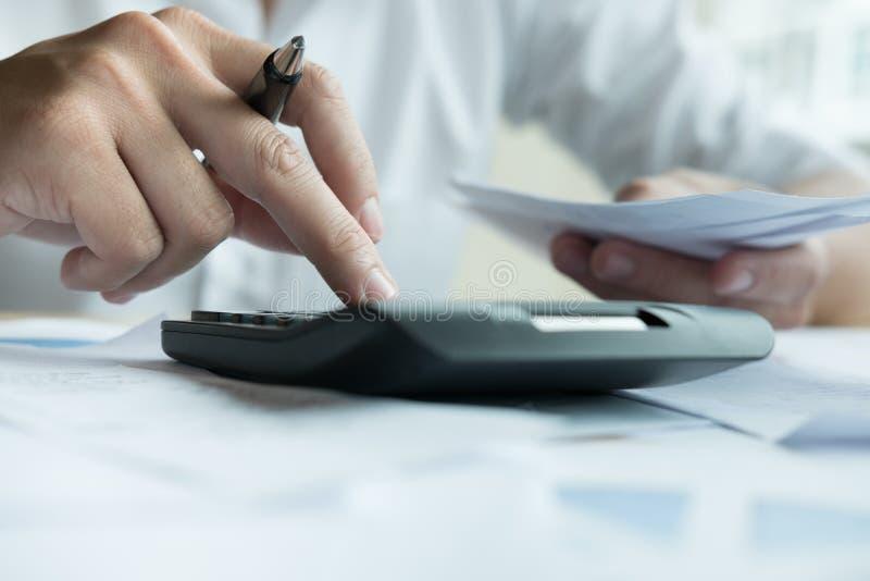 Mannen beräknar inhemska räkningar hemma Affärsman som använder calculat royaltyfria bilder