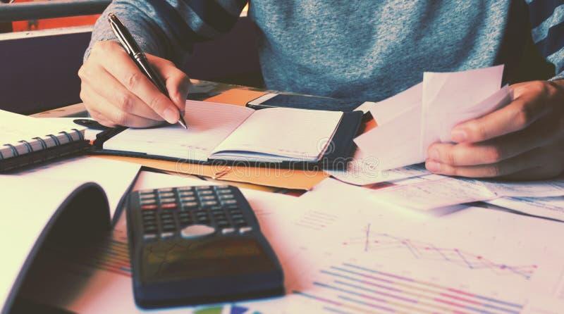 Mannen beräknar om kostnad, och handstil gör anmärkningen royaltyfri bild