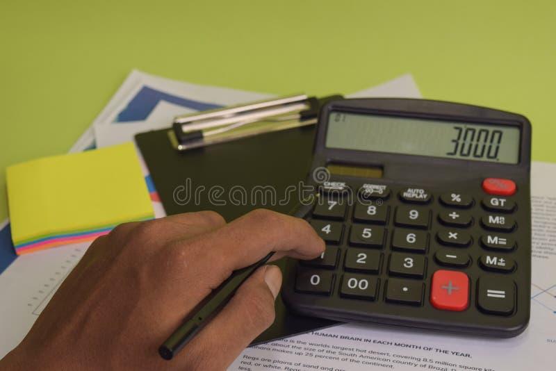 Mannen ber?knar finansiella budgetkostnad och analys Aff?rs- och finansbegrepp av kontorsskrivbordet arkivbilder