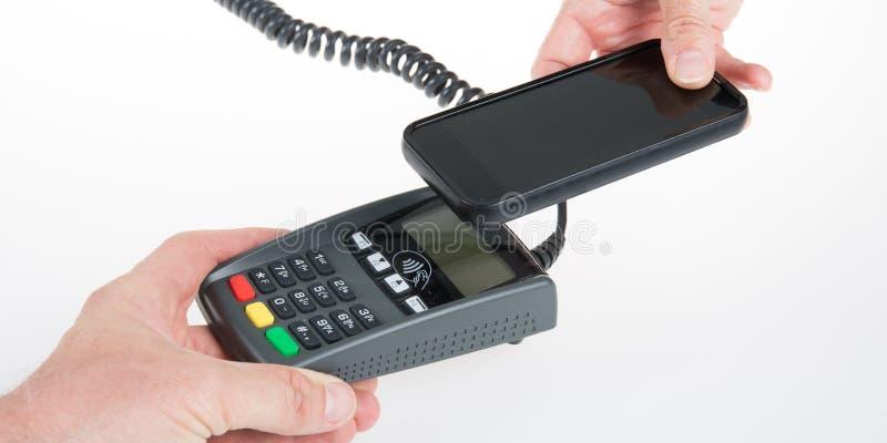 mannen betalar med smartphonen som använder NFC-teknologi shoppar in fotografering för bildbyråer