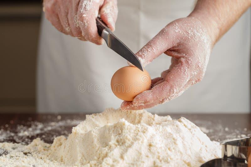 Mannen bryter ägget ovanför vitt mjöl för att göra deg för ravioli eller du arkivfoto