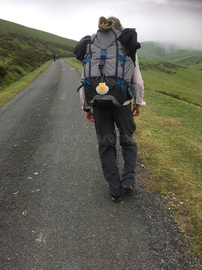 Mannen Camino vallfärdar att gå upp de branta Pyreneesna från St Jean arkivbild