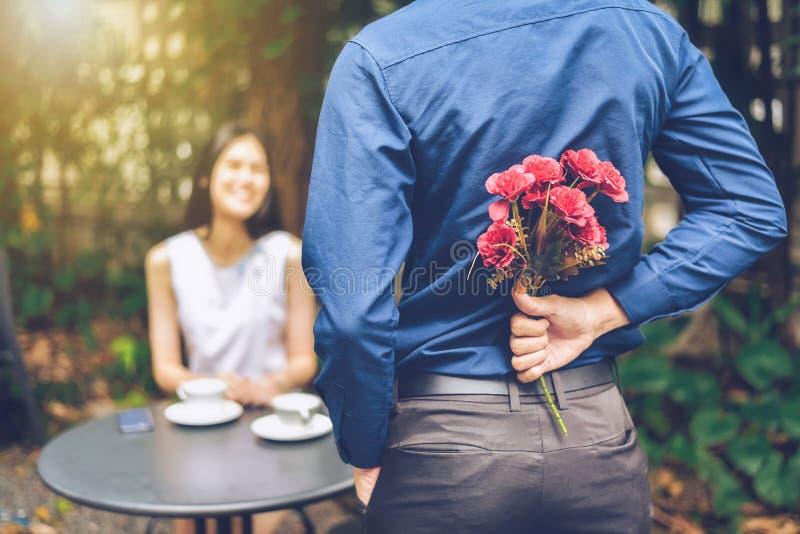 Mannen döljer röda blommor bak honom för att förvåna högt royaltyfri foto