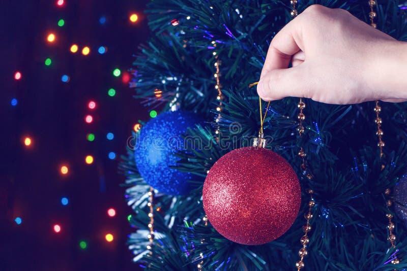 Mannen dekorerar julgranbollarna arkivfoto