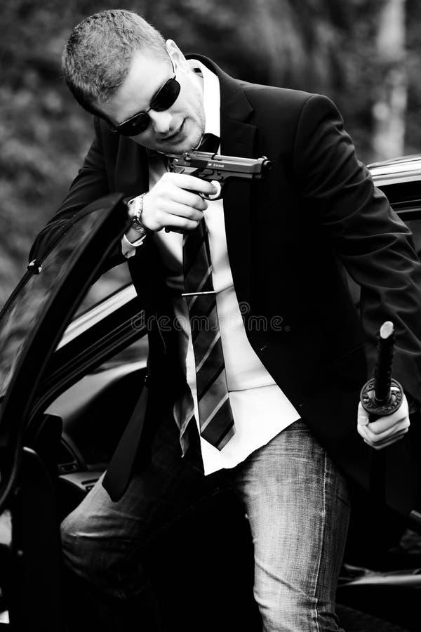 Mannen drar ett vapen i bil royaltyfri bild