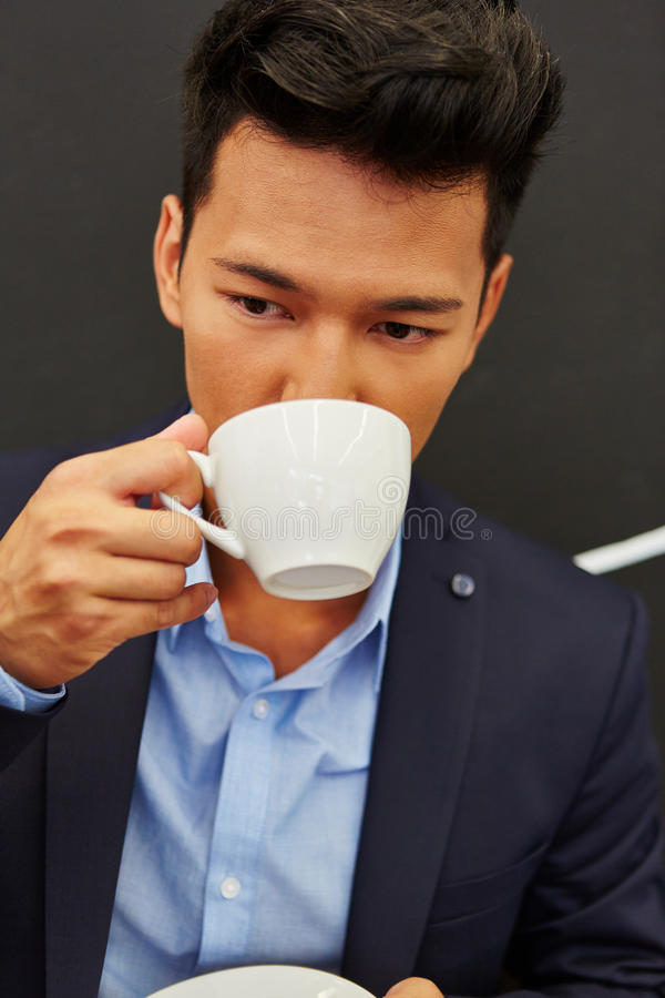 Mannen dricker coffe under hans avbrott royaltyfria bilder