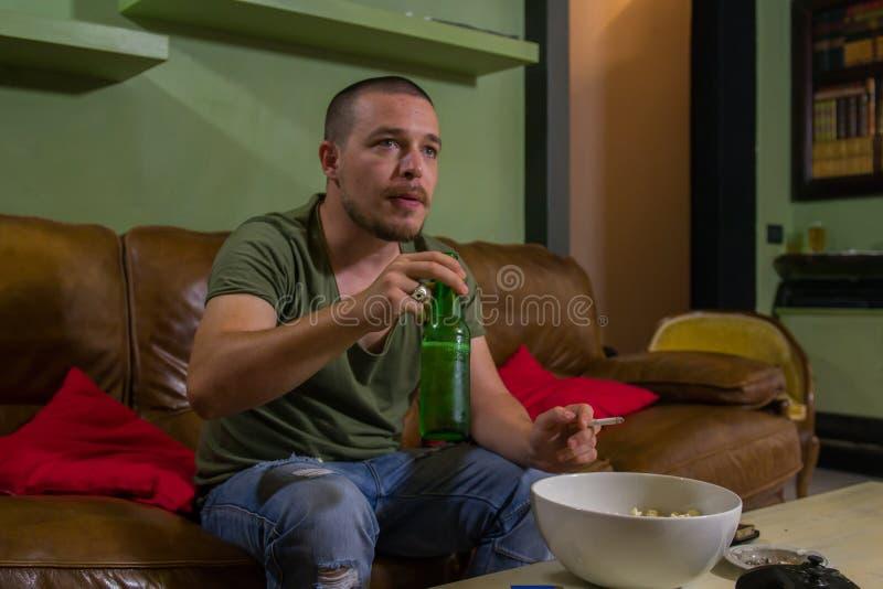 Mannen dricker ett öl, röker och håller ögonen på tv royaltyfri foto