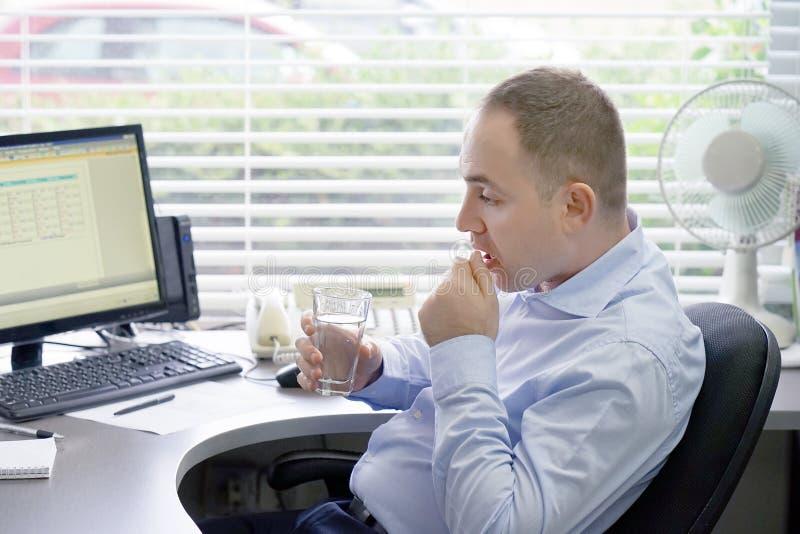 Mannen dricker ett piller från smärtar arkivfoto