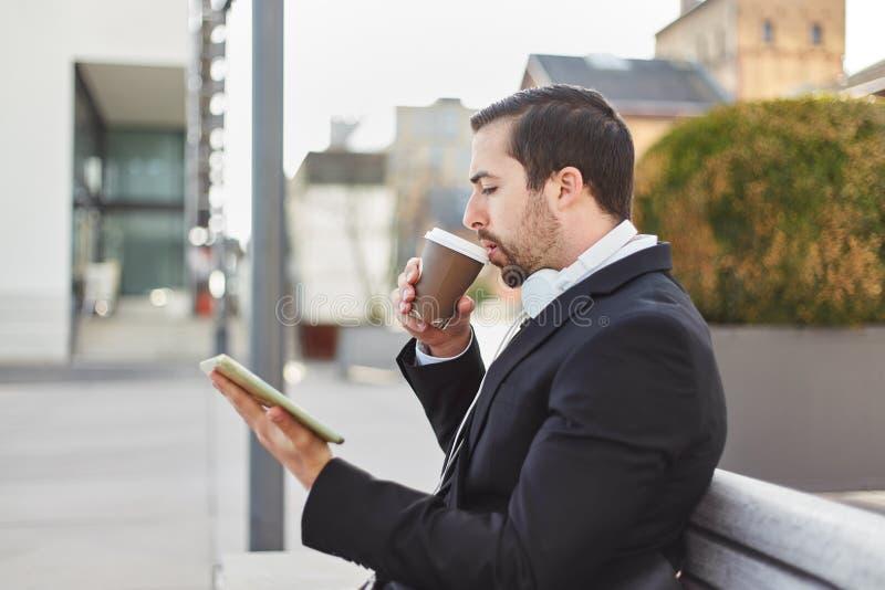 Mannen dricker kaffe och ser på minnestavlaPC royaltyfria bilder