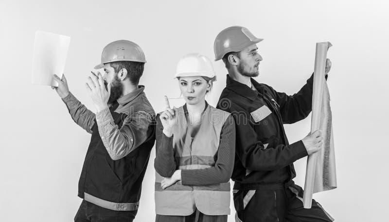 Mannen en vrouw in helmen onbezorgd met hamer en project, stock afbeeldingen