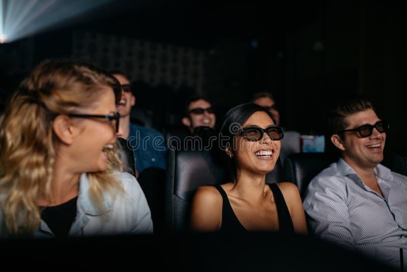 Mannen en vrouwen die op 3d film in theater letten stock foto