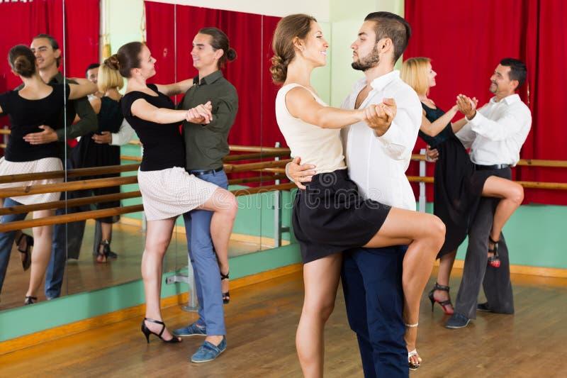 Mannen en vrouwen het genieten van van tango in klasse royalty-vrije stock fotografie