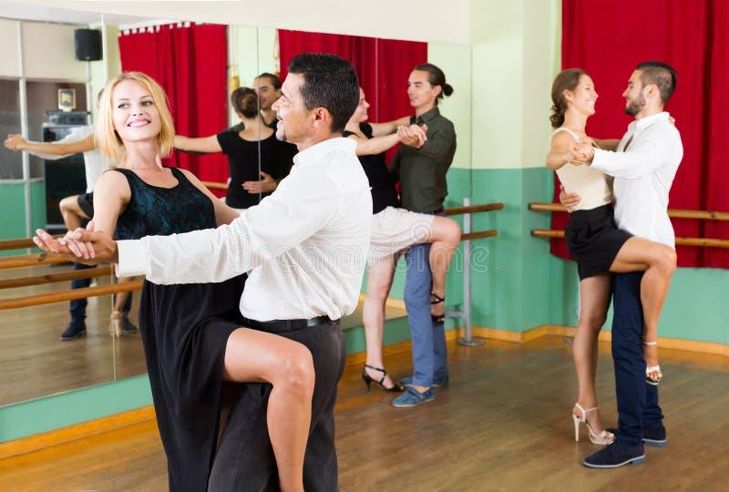 Mannen en vrouwen het genieten van van tango in klasse stock foto