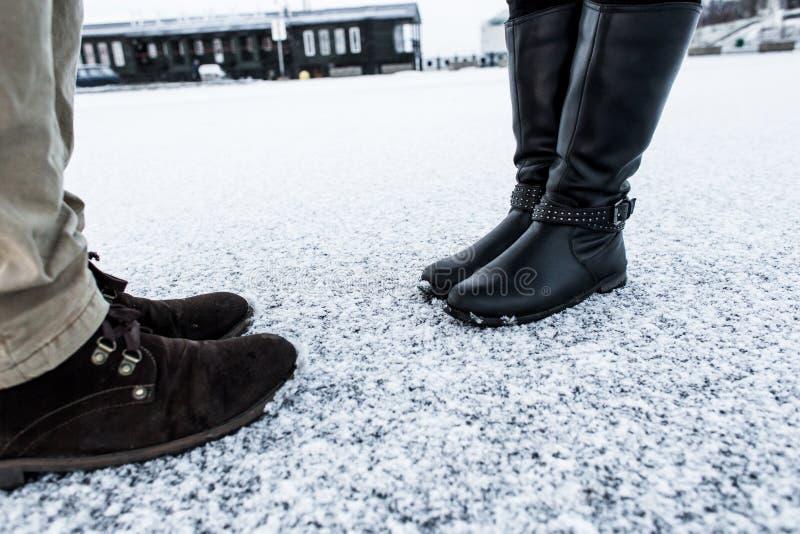 Mannen en vrouwen toevallige laarzen die zich op asfalt behandelde zanderige sneeuwoppervlakte bevinden R de Koude Winter Zachte  stock afbeelding
