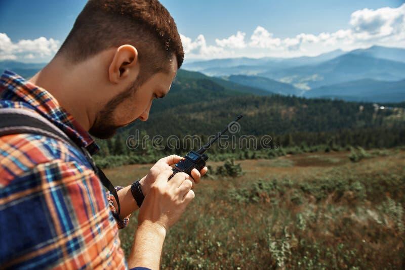 Mannen exploaterar radion, medan fotvandra i högland arkivfoton
