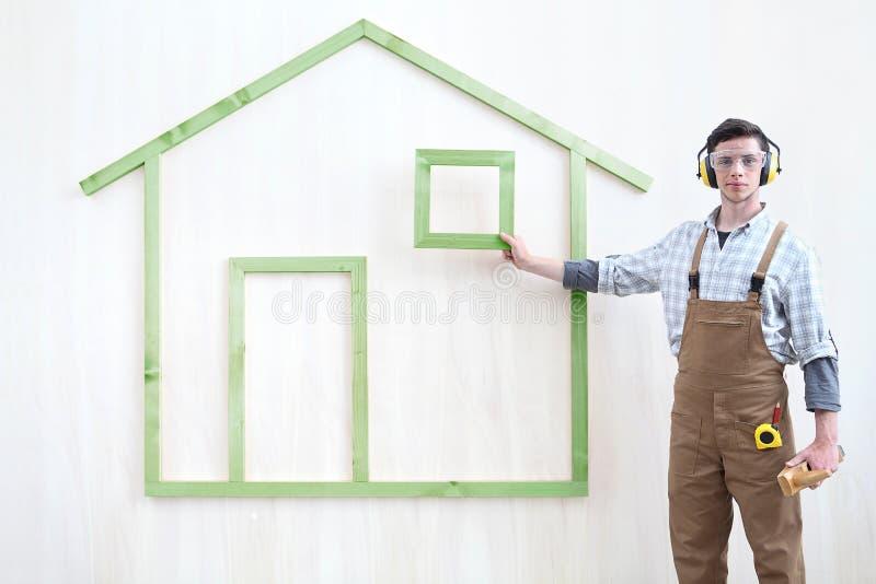 Mannen för arbetaren för snickaren för faktotumet för begreppet för huskonstruktionsrenovering visar modellen av det trägröna hus arkivbilder