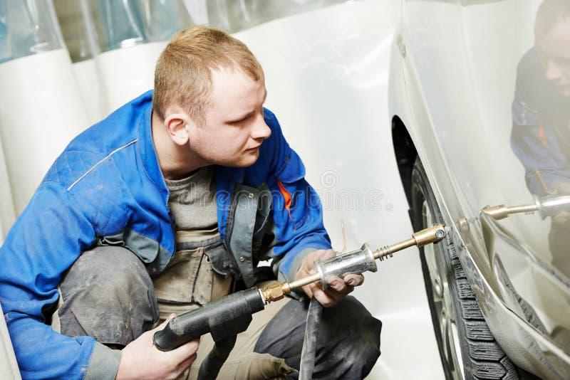 Mannen för den auto reparationen slätar metallkroppbilen ut arkivfoto