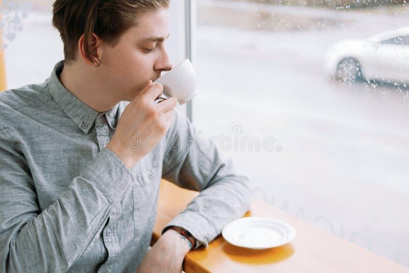 Mannen för kaffetefröjd tycker om koppdrinkkafét royaltyfria foton
