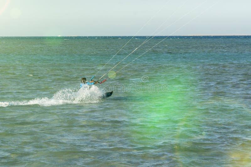 Mannen för Kitesurfing Kiteboarding handlingfoto bland vågor går snabbt En drakesurfare rider vågorna linsbelysning tonat royaltyfri bild