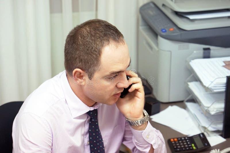 Mannen för kontorsarbetaren svarar appellen Affärsman som talar på telefonen på arbete royaltyfria foton
