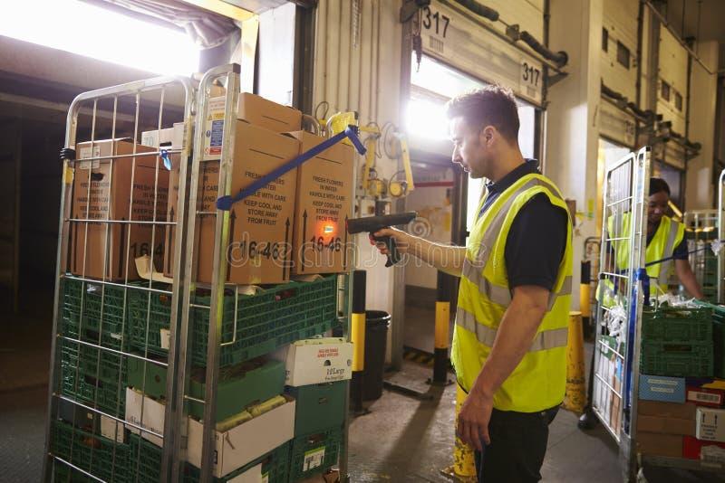 Mannen förbereder och avläser packar i ett lager för leverans arkivbild