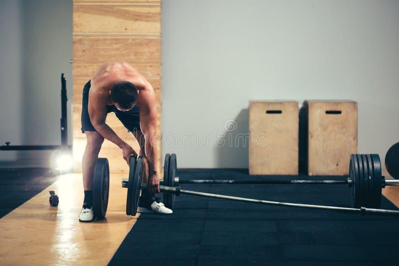 Mannen förbereder sig att göra övningar med skivstången i en idrottshall, uppehälleskivstångplatta i händer royaltyfri bild