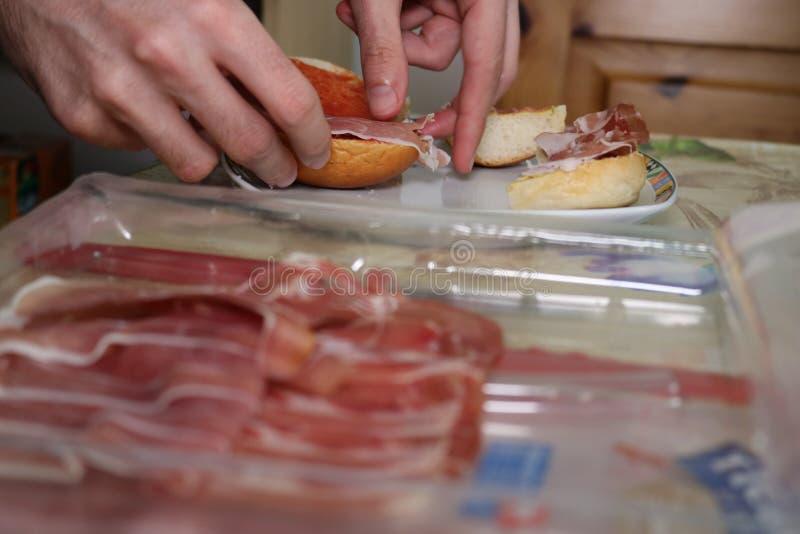 Mannen förbereder smörgåsen med prosciuttoskinka arkivfoto