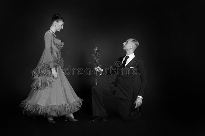 Mannen föreslår den lyckliga kvinnan med rosblomman fotografering för bildbyråer