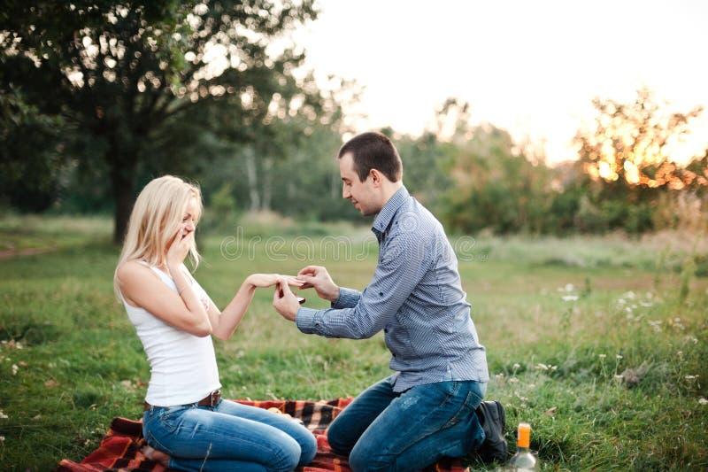 Mannen föreslår till en flicka i en parkera på en picknick royaltyfria foton