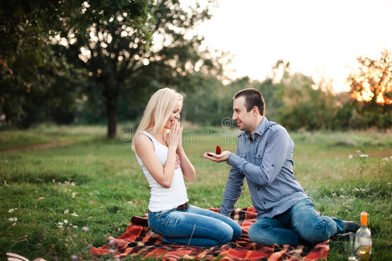 Mannen föreslår till en flicka i en parkera på en picknick royaltyfri bild
